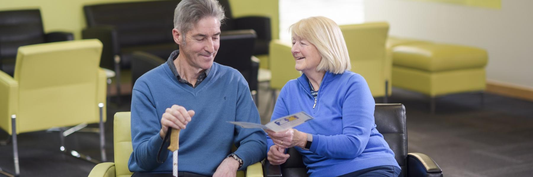Photograph of two adults sitting down, the woman is showing the man a leaflet