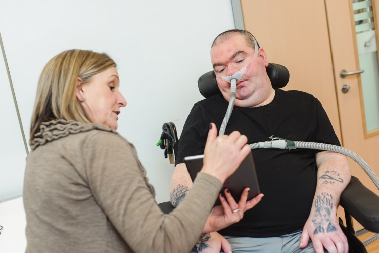 Researcher showing man with MND in wheelchair an ipad screen